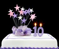 10th Cake. Fancy cake with number 10 candles.  Decorated with star-shapes and ribbons, in pastel tones Royalty Free Stock Photos