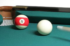 11 ball corner pocket. Pool ball number 09 in pool table near corner pocket and cue stock image