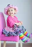 11 month old baby girl in pink dress-up clothes. A pretty 11-month-old baby is all dressed up in pink clothes and sits on a pink chair.  She has a pink and black Royalty Free Stock Images