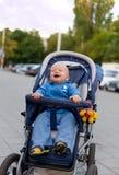 12个婴孩坐的微笑的婴儿推车 免版税库存照片