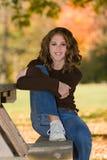 12 anos no banco da tabela de piquenique sob a árvore na queda Foto de Stock