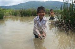 12,Dec,2016 - smile of kids from Churu people near by Dalat- Lam Dong- Vietnam. Some kids of Churu people drafting the fish near by Dalat- Lam Dong- Vietnam Royalty Free Stock Photography