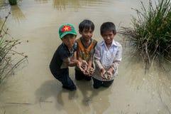 12,Dec,2016 - smile of kids from Churu people near by Dalat- Lam Dong- Vietnam. Some kids of Churu people drafting the fish near by Dalat- Lam Dong- Vietnam Royalty Free Stock Photos