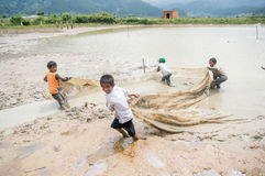 12,Dec,2016 -Some kids of Churu people drafting the fish near by Dalat- Lam Dong- Vietnam. Some kids of Churu people drafting the fish near by Dalat- Lam Dong Royalty Free Stock Photos
