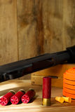12 Gauge Shotgun, Shells, and Clay Pigeons. Black 12 gauge pump action shotgun with shells, clay pigeons, and ear plugs sitting next to it Royalty Free Stock Photography