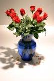 12 rosas rojas del vástago largo en florero Foto de archivo libre de regalías