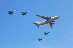 An-124 acepillan acompañado por el grupo del combatiente Su-27 Fotografía de archivo libre de regalías