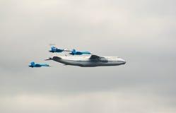 An-124 eskortiert durch Kämpfer Lizenzfreie Stockfotos