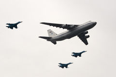 An-124 and Su-27. Three Sukhoi Su-27 Flanker fighters accompanying An-124 Ruslan over the Red Square Royalty Free Stock Image