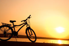 1269Bicycle. The bicycle silhouette is at seacoast on a sunset Royalty Free Stock Photography