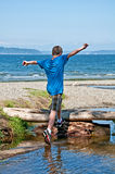 13 Year Old Boy Playing at Beach. This 13 year old Caucasian boy is running and jumping while playing at the beach.  His arms are held high in the air, ready to Royalty Free Stock Image