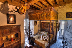 15th century Bunratty castle interior. BUNRATTY, IRELAND - FEB 19: Ancient bedroom interior of 15th century Bunratty castle, traditional Irish tourist attraction Royalty Free Stock Photos