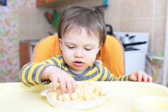 16 months baby eating corn curls Royalty Free Stock Image