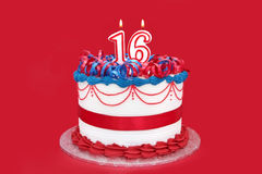 16th Cake. Sweet sixteen birthday cake, with numeral candles.  Vibrant red background Stock Image
