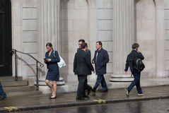 ЛОНДОН, ВЕЛИКОБРИТАНИЯ - 17-ОЕ СЕНТЯБРЯ 2015: Бизнесмены идя на улицу против стены Государственного банка Англии Стоковые Изображения RF