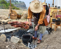 17th Century Pirate roasting a pig royalty free stock photography