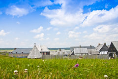 17th Century Village. A view of 17th century village rooftops behind a field of grass and wildflowers Stock Image