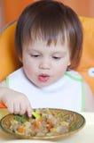 18个月吃蔬菜炖肉的婴孩 免版税库存照片