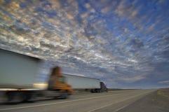 18 veículos com rodas que dirigem abaixo de um por do sol da estrada Fotografia de Stock Royalty Free