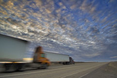 18 wheelers heading down a Highway sunset Royalty Free Stock Photography