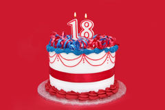 18th Cake. Eighteenth Birthday Cake, with numeral candles, on vibrant red background stock photos