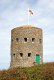18th century loophole tower Guernsey. 18th century defensive loophole tower c1778. Guernsey, Channel Islands. flag of Guernsey aloft Royalty Free Stock Photography