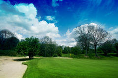 18th Hole. With bunker at the left side under beautifull blue sky with white clouds Stock Photography