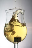 19_Dice in Wine. Dice being dropped and splashing into a glass of white wine Royalty Free Stock Image