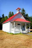 1908 School House. A typical white 1908 one room school house with a bell tower on the red metal roof. Trees and blue sky Stock Photography