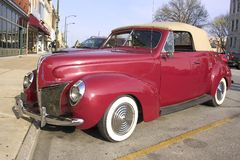 1939 Ford Convertible. Front and side view, large chrome grill.  The color is burgundy with a tan convertible top Stock Images