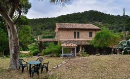 1948 villa at mallorca. Spanish stone villa with tile roof among hills and woods at mallorca built in 1948 stock photography