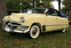 1950 Ford Custom Convertible. Bright yellow with a black top.  Wide whitewall tires, chrome grille and side trim.  A nice example of an original restored Stock Photo