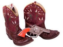 1950s child's cowgirl boots and cap pistol. All leather embroidered child's cowgirl boots from the 1950s, with a toy cap pistol from the same era Stock Images