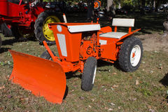 1960s Lawn and Garden Tractor. 1962 Jacobson Chief lawn tractor or mower.  Tractor has a push or snow blade, painted bright orange and white.  A nice restored Royalty Free Stock Photography