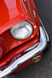 1965 Ford Mustang Head Light & Fender. Drivers side view of a 1965 Ford Mustang showing the front bumper, head light bucket and red.  Bright red automobile Royalty Free Stock Images