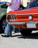 1968 Ford Mustang Owner & Car. Rear view of a 1968 Ford Mustang coupe and its owner Stock Image