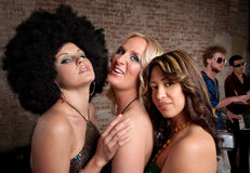 1970s Disco Music Party. Three cute ladies posing at a 1970s Disco Music Party. Horizontal shot royalty free stock photo