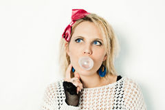 1980s girl blowing bubble gum. Portrait of a woman dressed in 1980s style thinking and blowing bubblegum royalty free stock photo