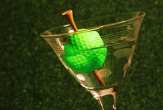 19th Hole. A golf ball olive with a tee toothpick in a martini against a black background (symbolic of the 19th hole in golf Royalty Free Stock Image