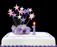 1st Cake. Fancy cake with number one candle.  Decorated with ribbons and star-shapes, in pastel tones on black background Stock Photography