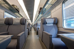 1st class modern train car Interior. Interior of an empty first class cabin in a modern European train car, featuring luxurious gray fabric seats with head rests Royalty Free Stock Photography