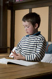 1st grade boy doing homework. 1st grade boy doing home work, counting fingers, striped shirt royalty free stock photos
