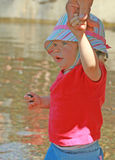 1st Time at the Lake. Decked out in her shade hat and having fetched a souvenir, this little girl is wondering what other fun adventures await Royalty Free Stock Photography