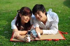 2个亚洲夫妇公园电话年轻人 免版税库存图片