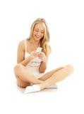2个楼层坐少年白色的女孩电话 免版税图库摄影