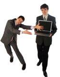 2个生意人膝上型计算机显示二年轻人 免版税库存图片