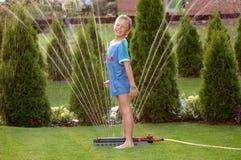 2个男孩儿童庭院喷水隆头 图库摄影