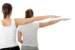 2个美丽的执行的执行womans瑜伽年轻人 免版税库存图片