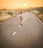 2女孩她滑板走 免版税图库摄影