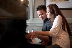 2对亚洲夫妇钢琴使用 免版税库存照片